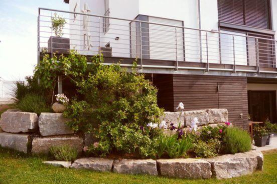 Ausschnitt eines Familiengartens mit moderner Gartengestaltung. Natursteinmauer mit Beet.