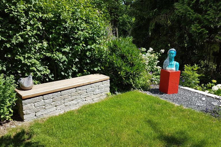 Gartenplanung mit Natursteinsitzmauer mit Holzauflage.