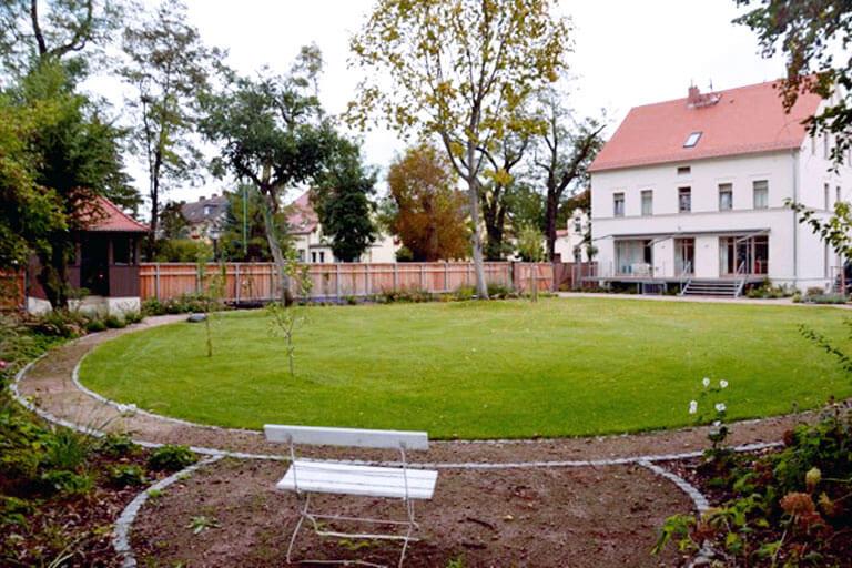 Gartenplanung in Magdeburg. Rundblick in die Gartenanlage mit Wohnhaus, Gartenhaus und geschützter Sitznische.