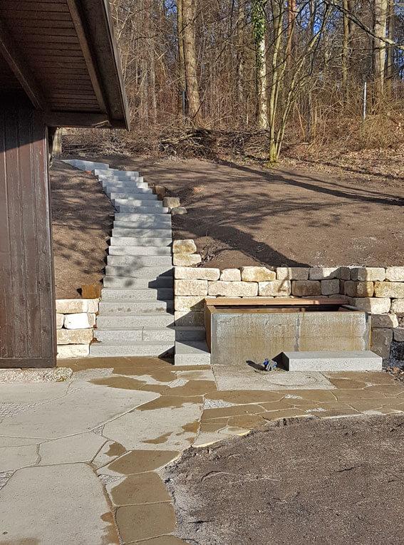Gartengestaltung mit Natursteinmauer und modernem Wasserbecken aus Cortenstahl.