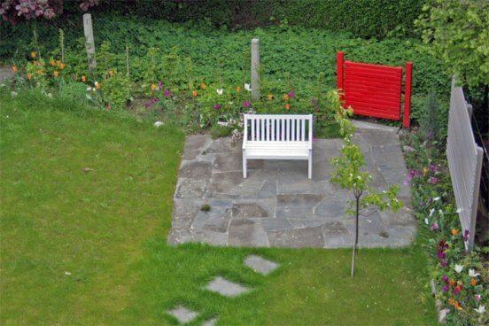 Sitzplatz mit rotem Gartentor und Sichtschutzelemente